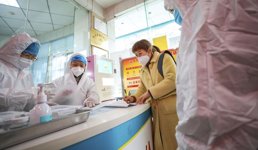 Medical workers in protective gear talk with a woman suspected of being ill with a coronavirus at a community health station in Wuhan in central China's Hubei Province, Monday, Jan. 27, 2020. China on Monday expanded sweeping efforts to contain a viral disease by extending the Lunar New Year holiday to keep the public at home and avoid spreading infection. (Chinatopix via AP)  **FILE**