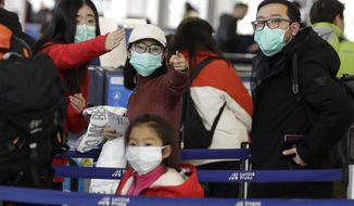 Passengers wearing masks wait in a line to check-in to a flight to Shanghai at the Vaclav Havel International Airport in Prague, Czech Republic, Monday, Jan. 27, 2020. Prague's international airport is launching an information campaign for travellers who develop symptoms possibly linked to a new coronavirus illness. (AP Photo/Petr David Josek)