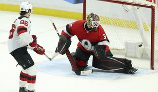 New Jersey Devils centre Jack Hughes (86) scores past Ottawa Senators goaltender Marcus Hogberg (35) during a shoot-out in NHL hockey action in Ottawa on Monday, Jan. 27, 2020. (Fred Chartrand/The Canadian Press via AP)