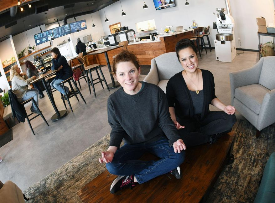 In this Jan. 10, 2020 photo, Balancing Goat Coffee Co. co-owners Karen Schmidt, left, and Dawn Hager poose in their specialty coffee, pastries, fresh fruit, smoothies, sandwiches and wellness studio at a strip mall in Mandan, N.D. (Mike McCleary/The Bismarck Tribune via AP)