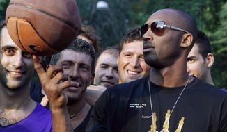 """FILE - In this Sept. 28, 2011, file photo, U.S. basketball star Kobe Bryant plays with a ball during a sponsor's appearance in Milan, Italy. In Europe where Bryant grew up, the retired NBA star is being remembered for his """"Italian qualities."""" Italian basketball federation president Giovanni Petrucci tells The Associated Press that Bryant is """"particularly important to us because he knew Italy so well, having lived in several cities here.  He had a lot of Italian qualities."""" (AP Photo/Luca Bruno, File)"""