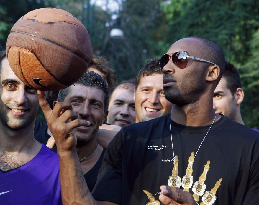 "FILE - In this Sept. 28, 2011, file photo, U.S. basketball star Kobe Bryant plays with a ball during a sponsor's appearance in Milan, Italy. In Europe where Bryant grew up, the retired NBA star is being remembered for his ""Italian qualities."" Italian basketball federation president Giovanni Petrucci tells The Associated Press that Bryant is ""particularly important to us because he knew Italy so well, having lived in several cities here.  He had a lot of Italian qualities."" (AP Photo/Luca Bruno, File)"