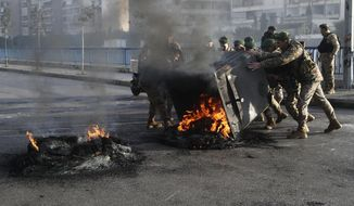 Lebanese army soldiers try to remove burning tires which were set on fire by the anti-government protesters to block the southern entrance of a highway during a protest against the newly formed cabinet, in Beirut, Lebanon, Monday, Jan. 27, 2020. (AP Photo/Hussein Malla)