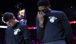 Miami Heat forward Udonis Haslem, right, covers his face as he stands with Tyler Herro during the national anthem following a tribute for NBA basketball player Kobe Bryant before a game against the Orlando Magic, Monday, Jan. 27, 2020, in Miami. Bryant and his daughter were among those who died in a helicopter crash Sunday in California. (AP Photo/Lynne Sladky)