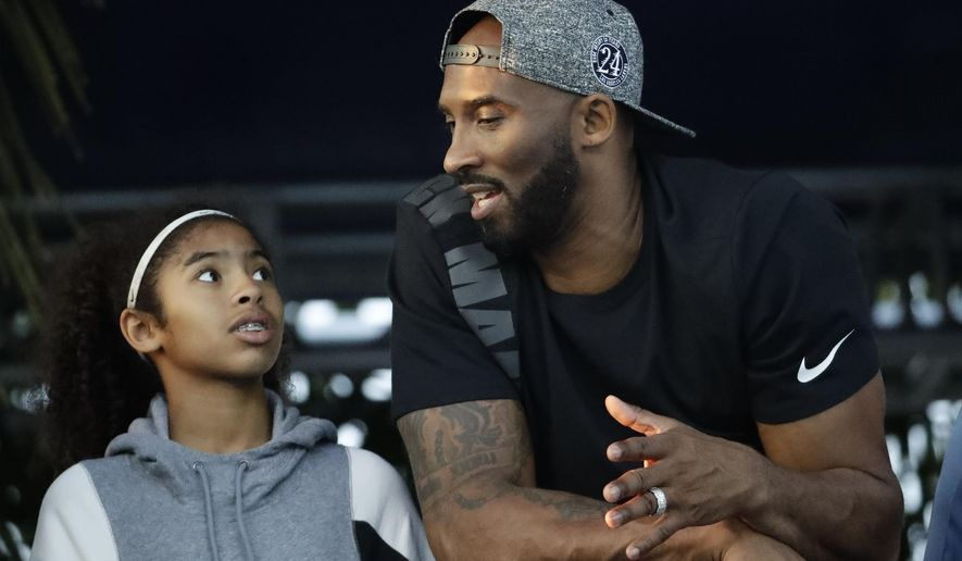 In this July 26, 2018 file photo former Los Angeles Laker Kobe Bryant and his daughter Gianna watch the U.S. national championships swimming meet in Irvine, Calif. Bryant, the 18-time NBA All-Star who won five championships and became one of the greatest basketball players of his generation during a 20-year career with the Los Angeles Lakers, died in a helicopter crash Sunday, Jan. 26, 2020. Gianna also died in the crash. (AP Photo/Chris Carlson, file)