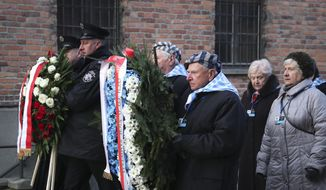 Survivors carry a wreath at the Auschwitz Nazi death camp in Oswiecim, Poland, Monday, Jan. 27, 2020. Survivors of the Auschwitz-Birkenau death camp gathered for commemorations marking the 75th anniversary of the Soviet army's liberation of the camp, using the testimony of survivors to warn about the signs of rising anti-Semitism and hatred in the world today. (AP Photo/Czarek Sokolowski)
