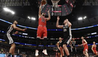 Chicago Bulls guard Tomas Satoransky (31) goes to the basket as San Antonio Spurs center Jakob Poeltl (25) defends him during the first half of an NBA basketball game Monday, Jan. 27, 2020, in Chicago. (AP Photo/David Banks)