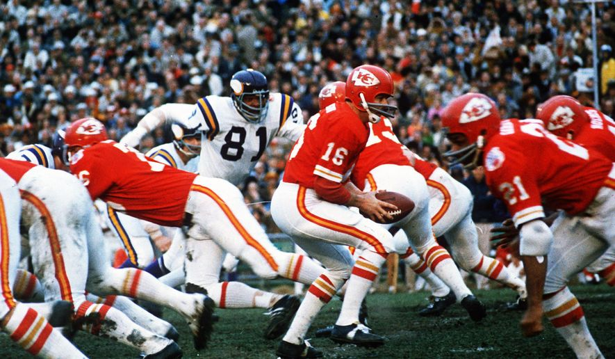 FILE - In this Jan. 11, 1970, file photo, Kansas City Chiefs quarterback Len Dawson (16) turns around to hand the ball off to running back Mike Garrett (21) during the Super Bowl IV football game in New Orleans.  As the Chiefs prepare to play the San Francisco 49ers on Sunday, Feb. 2, 2020, many members of the 1970 team never lived to see the the Chiefs return to the championship game, and many others are in failing health.    (AP Photo/File)