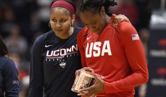 Minnesota Lynx and former Connecticut player Maya Moore, left, puts her arm around former Connecticut teammate and New York Liberty player Tina Charles during a ceremony honoring their championship team before an exhibition basketball game between Connecticut and the United States, Monday, Jan. 27, 2020, in Hartford, Conn. (AP Photo/Jessica Hill)
