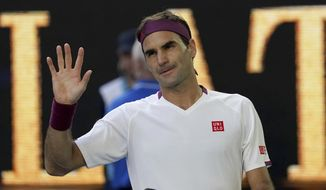 Switzerland's Roger Federer waves after defeating Tennys Sandgren of the U.S. in their quarterfinal match at the Australian Open tennis championship in Melbourne, Australia, Tuesday, Jan. 28, 2020. (AP Photo/Lee Jin-man)