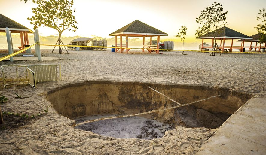 A sinkhole is surrounded by police tape after it appeared when a powerful magnitude 7.7 earthquake struck in the Caribbean Sea between Jamaica and eastern Cuba, at Public Beach on West Bay, Grand Cayman, Tuesday, Jan. 28, 2020. The quake also hit the Cayman Islands, leaving cracked roads and what appeared to be sewage spilling from cracked mains. There were no immediate reports of deaths, injuries or more severe damage. (Taneos Ramsay/Cayman Compass via AP)