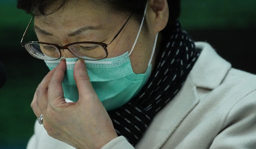 Hong Kong Chief Executive Carrie Lam adjusts protective face mask during a press conference held in Hong Kong, Tuesday, Jan. 28, 2020. Lam has announced that all rail links to mainland China will be cut starting Friday as fears grow about the spread of a new virus. (AP Photo/Vincent Yu)