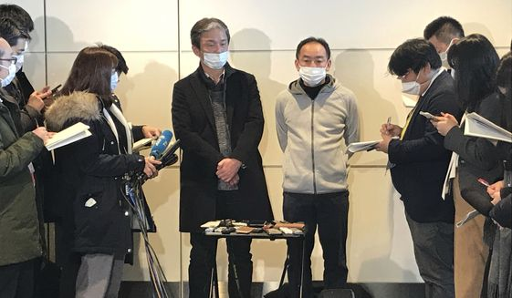 Wearing surgical masks, Takeo Aoyama, center left, and Takayuki Kato, center right, employees at Nippon Steel Corp.s subsidiary in Wuhan, China, speak to journalists after returning home by a Japanese chartered plane at Haneda international airport in Tokyo Wednesday, Jan. 29, 2020. Japan on Wednesday began evacuating their citizens from the Chinese city hardest-hit by an outbreak of a new virus. Aoyama said more than 400 Japanese people wishing to return to Japan are in Wuhan. (AP Photo/Haruka Nuga)