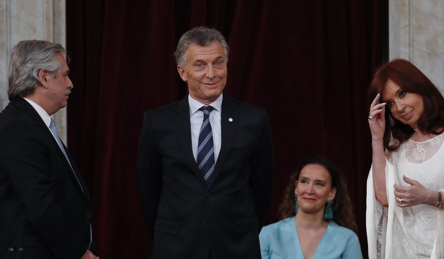 Outgoing president Mauricio Macri gestures before giving the presidential sash to new President Alberto Fernandez, left, at the Congress in Buenos Aires, Argentina, Tuesday, Dec. 10, 2019. At right is Vice President Cristina Fernandez de Kirchner. (AP Photo/Natacha Pisarenko)