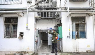 A government worker sprays disinfectant on a residential building in Wuhan in central China's Hubei Province, Tuesday, Jan. 28, 2020. Hong Kong's leader announced Tuesday that all rail links to mainland China will be cut starting Friday as fears grow about the spread of a new virus. (Chinatopix via AP)