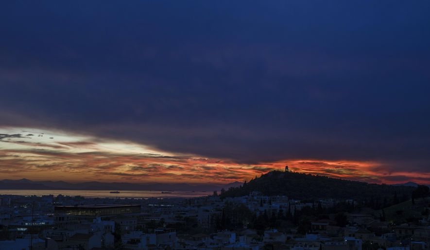 The sun sets behind the lighted ancient Philopappu monument, right, and the Saronic golf, left, during a cloudy day in Athens, on Monday Dec. 2, 2019. (AP Photo/Petros Giannakouris)