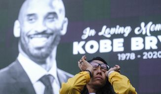 Nicole Mascarenhas, wipes her eyes in front of a screen with the late Kobe Bryant at a memorial for Kobe Bryant near Staples Center Monday, Jan. 27, 2020, in Los Angeles. Bryant, the 18-time NBA All-Star who won five championships and became one of the greatest basketball players of his generation during a 20-year career with the Los Angeles Lakers, died in a helicopter crash Sunday. (AP Photo/Ringo H.W. Chiu)