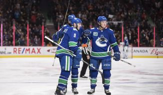 Vancouver Canucks' J.T. Miller, front left, Jake Virtanen, right, and Jake Virtanen, back left, celebrate Miller's first goal against the St. Louis Blues during the second period of an NHL hockey game in Vancouver, British Columbia on Monday Jan. 27, 2020. (Darryl Dyck/The Canadian Press via AP)