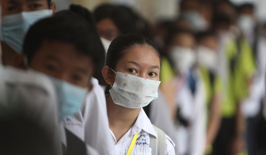 Students line up to sanitize their hands to avoid the contact of coronavirus before their morning class at a hight school in Phnom Penh, Cambodia, Tuesday, Jan. 28, 2020. China on Tuesday reported 25 more deaths from a new viral disease, as the U.S. government prepared to fly Americans out of the city at the center of the outbreak. (AP Photo/Heng Sinith)