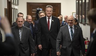 Sen. John Coghill, R-North Pole, right, and Rep. Gary Knopp, R-Kenai, left, escort Gov. Mike Dunleavy to the House chambers to deliver his State of the State speech to a Joint Session of the Alaska Legislature at the Alaska State Capitol in Juneau, Alaska, on Monday, Jan. 27, 2020. (AP Photo/Michael Penn)