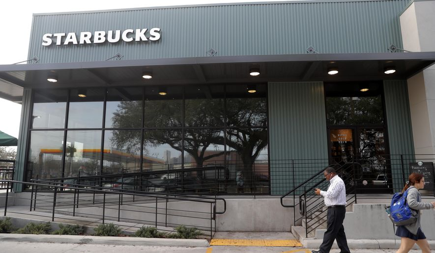 FILE - In this Jan. 16, 2020, file photo customers come and go at a Starbucks on South Claiborne Ave. in New Orleans. Starbucks Corp. reports financial earns on Tuesday, Jan. 28. (AP Photo/Gerald Herbert, File)