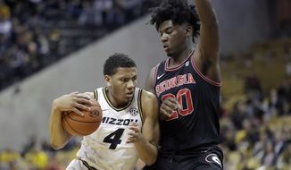 Missouri's Javon Pickett (4) heads to the basket past Georgia's Rayshaun Hammonds (20) during the second half of an NCAA college basketball game Tuesday, Jan. 28, 2020, in Columbia, Mo. Missouri won 72-69. (AP Photo/Jeff Roberson)
