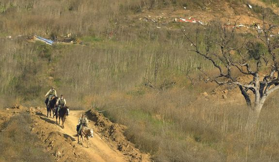 Sheriff's deputies on horseback leave the scene of a helicopter crash, Monday, Jan. 27, 2020, that killed former NBA basketball player Kobe Bryant, his 13-year-old daughter, Gianna, and seven others, in Calabasas, Calif., on Sunday. (AP Photo/Mark J. Terrill)