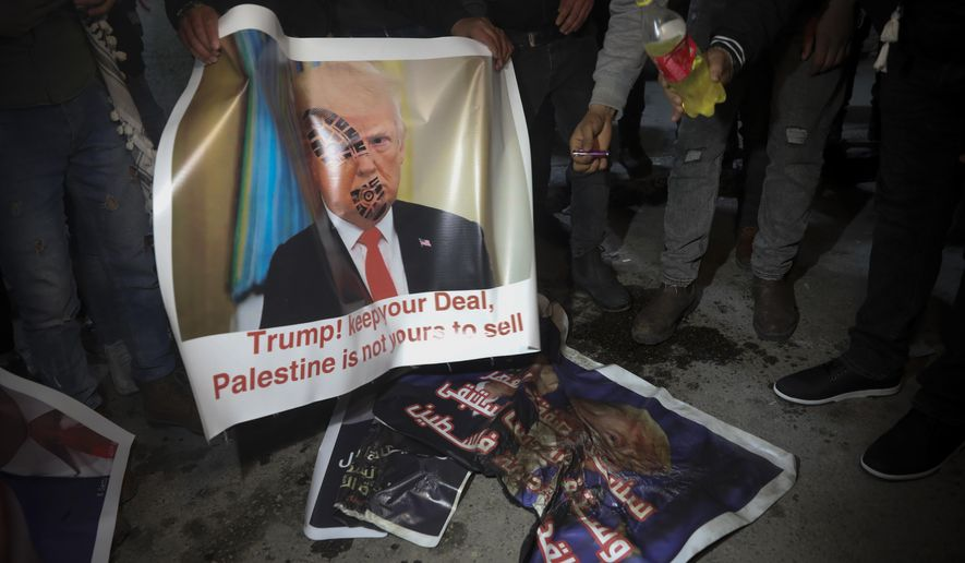 """Palestinian hold a poster showing U.S. President Donald Trump as they protest the American peace plan in Bethlehem, Monday, Jan. 27, 2020. Israeli Prime Minister Benjamin Netanyahu arrived in Washington Sunday night vowing to """"make history"""" at a planned meeting with President Donald Trump for the unveiling of the U.S. administration's much-anticipated plan to resolve the Israeli-Palestinian conflict. (AP Photo/Mahmoud Illean)"""