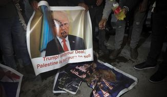 "Palestinian hold a poster showing U.S. President Donald Trump as they protest the American peace plan in Bethlehem, Monday, Jan. 27, 2020. Israeli Prime Minister Benjamin Netanyahu arrived in Washington Sunday night vowing to ""make history"" at a planned meeting with President Donald Trump for the unveiling of the U.S. administration's much-anticipated plan to resolve the Israeli-Palestinian conflict. (AP Photo/Mahmoud Illean)"