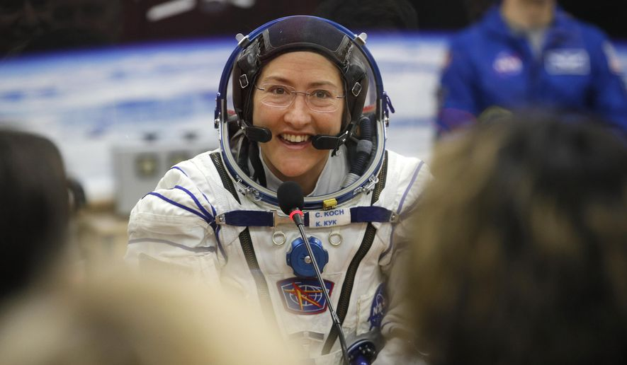 In this Thursday, March 14, 2019, file photo, U.S. astronaut Christina Koch, member of the main crew of the expedition to the International Space Station (ISS), speaks with her relatives through a safety glass prior the launch of Soyuz MS-12 space ship at the Russian leased Baikonur cosmodrome, Kazakhstan. (AP Photo/Dmitri Lovetsky, Pool)