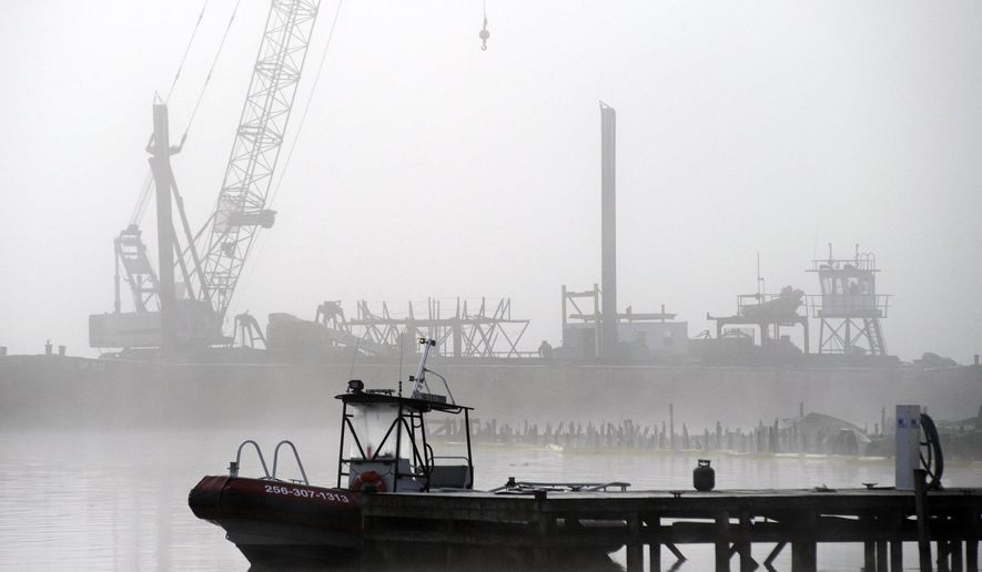 A salvage crane shrouded in fog rises above a barge in a creek near the Tennessee River at the scene of a fatal marina fire at Scottsboro, Ala., on Tuesday, Jan. 28, 2020. Crews already have removed at least two boats that burned at Jackson County Park Marina, and authorities say it could take several days to recover all 35 of the boats that burned in the blaze. (AP Photo/Jay Reeves)