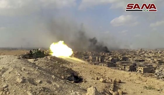This file frame grab from a video released on Nov. 2, 2017, by the Syrian official news agency SANA shows a Syrian army tank firing during a battle against Islamic State militants in Deir el-Zour, Syria. The Islamic State group seemed largely defeated last year, with the loss of its territory, the killing of its founder in a U.S. raid and an unprecedented crackdown on its social media propaganda machine but tensions between the U.S. and Iran in the region provide a comeback opportunity for the extremist group. (SANA via AP, File)