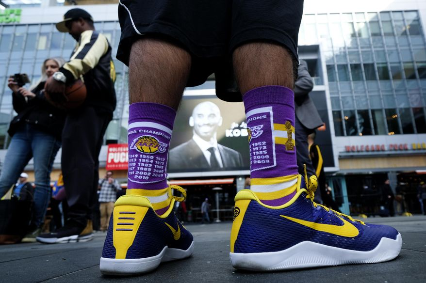 A fan stands in front of a screen with the late Kobe Bryant at a memorial for Kobe Bryant near Staples Center Monday, Jan. 27, 2020, in Los Angeles. Bryant, the 18-time NBA All-Star who won five championships and became one of the greatest basketball players of his generation during a 20-year career with the Los Angeles Lakers, died in a helicopter crash Sunday. (AP Photo/Ringo H.W. Chiu) ** FILE **