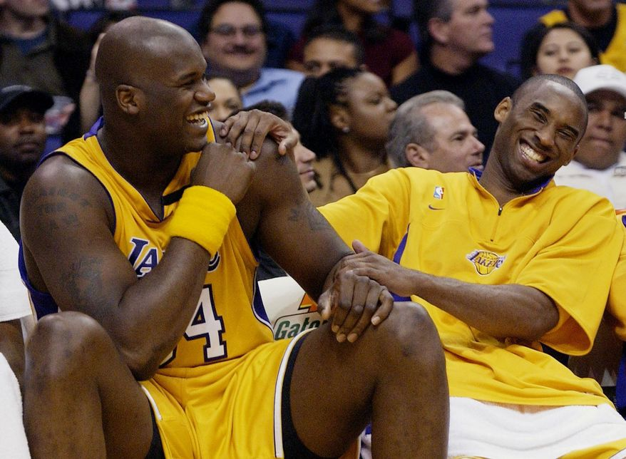 FILE - In this April 15, 2003, file photo, Los Angeles Lakers Shaquille O'Neal, left, and Kobe Bryant share a laugh on the bench while their teammate take on the Denver Nuggets during the fourth quarter at Staples Center in Los Angeles. Bryant, the 18-time NBA All-Star who won five championships and became one of the greatest basketball players of his generation during a 20-year career with the Los Angeles Lakers, died in a helicopter crash Sunday, Jan. 26, 2020. (AP Photo/Kevork Djansezian, File)