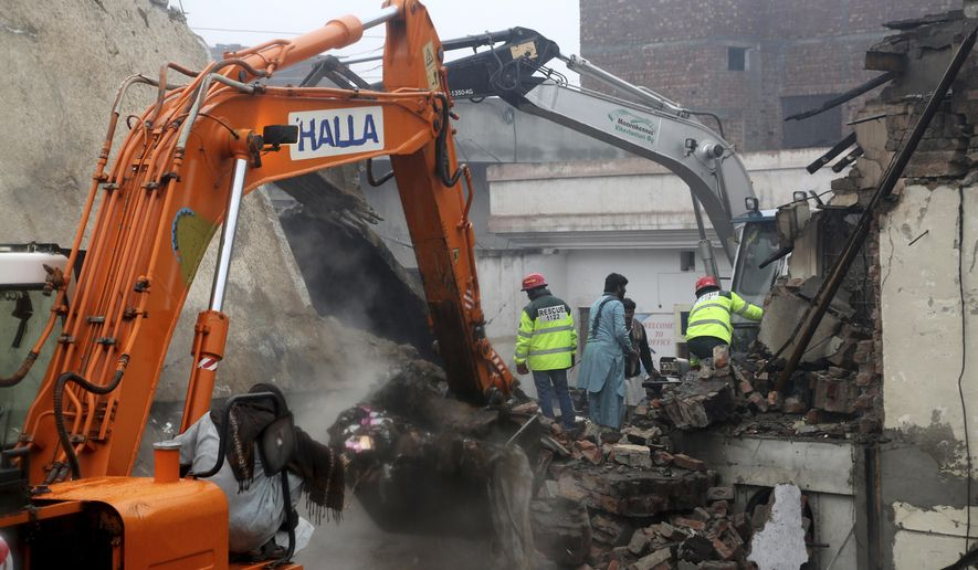 Pakistani rescue workers look for survivors amid debri of a building in Lahore, Pakistan, Tuesday, Jan. 28, 2020. Pakistani officials said Tuesday that a gas cylinder explosion at a small perfume-making factory killed many people and injured others. (AP Photo/K.M. Chaudhry)