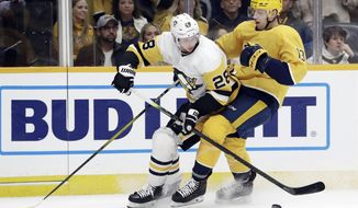 Pittsburgh Penguins defenseman Marcus Pettersson (28), of Sweden, and Nashville Predators center Nick Bonino (13) chase the puck during the second period of an NHL hockey game Friday, Dec. 27, 2019, in Nashville, Tenn. (AP Photo/Mark Humphrey)
