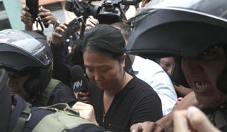 Keiko Fujimori, the daughter of Peru's former President Alberto Fujimori and opposition leader is escorted by police in Lima, Peru, Tuesday, Jan. 28, 2020. In a court session a judge decided she must return to preventive detention pending a corruption investigation. (AP Photo/Martin Mejia)