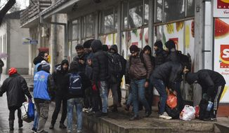 Migrants gather in front of a supermarket in central Horgos, Serbia, near the Hungarian border, Tuesday, Jan. 28, 2020. Earlier Tuesday some sixty migrants tried to break through the border fence illegally into Hungary from Serbia. A small group managed to enter Hungarian territory, while others were prevented by police to cross the border. Some of the intruders have been arrested. (Edvard Molnar/MTI via AP)