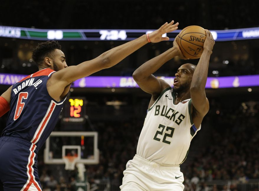 Milwaukee Bucks' Khris Middleton puts up a shot against Washington Wizards' Troy Brown Jr. during during the second half of an NBA basketball game Tuesday, Jan. 28. 2020, in Milwaukee. (AP Photo/Jeffrey Phelps)