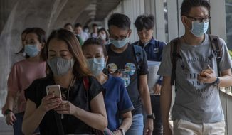 Thai people wearing face masks walk in a overhead bridge in Bangkok, Thailand, Wednesday, Jan. 29, 2020. Tourism Council of Thailand said Tuesday that new coronavirus outbreak estimated to cost 50 billion Bhat (1,613,892 US Dollars) in lost tourism income for Thailand's economy due to China's blanket ban on tourists leaving its effected cities. (AP Photo/Gemunu Amarasinghe)