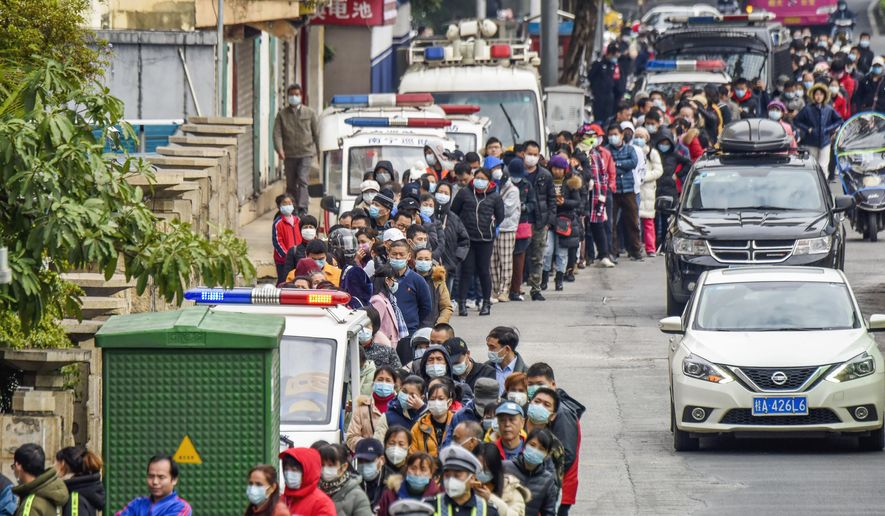 People line up to buy face masks from a medical supply company in Nanning in southern China's Guangxi Zhuang Autonomous Region, Wednesday, Jan. 29, 2020. Countries began evacuating their citizens Wednesday from the Chinese city hardest-hit by a new virus that has now infected more people in China than were sickened in the country by SARS. (Chinatopix via AP)