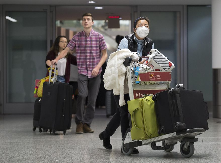 """A woman wears a mask following the outbreak of a new virus as people arrive from the International terminal at Toronto Pearson International Airport in Toronto on Saturday, Jan. 25, 2020. A Toronto hospital said Saturday it has a confirmed case of the deadly virus from China, Canada's first. Sunnybrook Health Sciences Centre said it is """"caring for a patient who has a confirmed case of the novel coronavirus that originated in Wuhan, China."""" (Nathan Denette/The Canadian Press via AP)"""