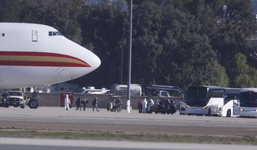 Passengers board buses after arriving on an airplane carrying U.S. citizens being evacuated from Wuhan, China, at March Air Reserve Base in Riverside, Calif. Jan. 29, 2020.  The passengers will undergo additional screenings in California and be placed in temporary housing. Officials have not said how long they will stay there.  (AP Photo/Ringo H.W. Chiu)