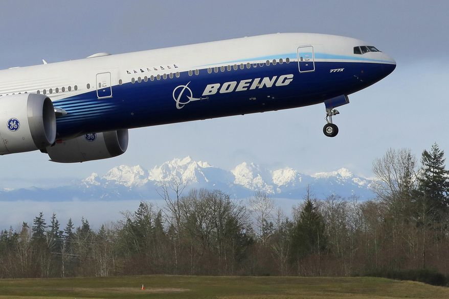 In this Jan. 25, 2020, file photo a Boeing 777X airplane takes off on its first flight with the Olympic Mountains in the background at Paine Field in Everett, Wash. Boeing Co. reports financial results on Wednesday, Jan. 29. (AP Photo/Ted S. Warren, File)  **FILE**