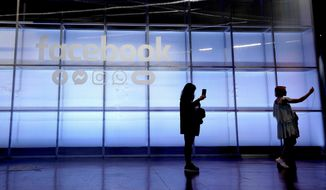 FILE - In this April 30, 2019, file photo attendees take a selfie in front of a Facebook sign at F8, the Facebook's developer conference in San Jose, Calif. Facebook reports financial results on Wednesday, Jan. 29, 2020. (AP Photo/Tony Avelar, File)