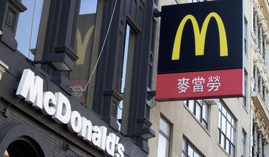 FILE - In this Jan. 22, 2020, file photo signs for a McDonald's restaurant hang on a building in the Chinatown section of New York. McDonald's reports financial results on Wednesday, Jan. 29. (AP Photo/Mark Lennihan, File)