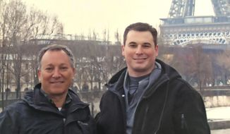 """In this undated photo made available by the Modell family, Ryan Modell, right, visits Paris with his father Sandy Modell. Sandy Modell is asking Florida Gov. Ron DeSantis to reopen the investigation into his son's 2016 shooting death during an altercation at Ryan Modell's Fort Myers, Fla., condominium complex. Local prosecutors declined to charge the shooter, Steve Taylor, citing the state's """"stand your ground"""" law, a decision Sandy Modell wants reversed. (Modell family via AP)"""