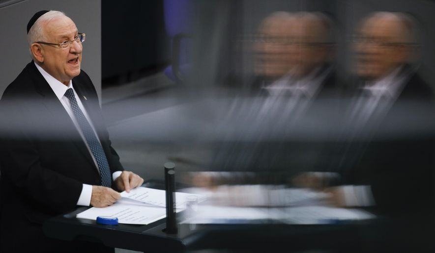 This photo taken with reflections in windows at the visitors tribune, Israel's President Reuven Rivlin delivers his speech during a special meeting of the German Parliament Bundestag commemorating the victims of the Holocaust in Berlin, Germany, Wednesday, Jan. 29, 2020. (AP Photo/Markus Schreiber)
