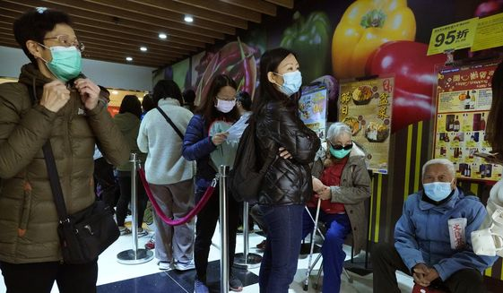 People queue up waiting to purchase face masks outside a shop in Hong Kong, Wednesday, Jan. 29, 2020. A viral outbreak that began in China has infected more than 6,000 people in the mainland and more than a dozen other countries. (AP Photo/Vincent Yu)
