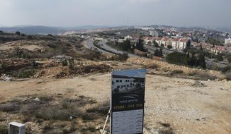 A new housing project sign stands in the Jewish West Bank settlement of Ari'el, Tuesday, Jan. 28, 2020. The population of Jewish settlements in the West Bank surged by more than 3% in 2019, well above the growth rate of Israel's overall population, a settler group said Tuesday. It predicted even higher growth this year thanks to a nascent building boom made possible by friendly policies of the Trump administration. (AP Photo/Ariel Schalit)